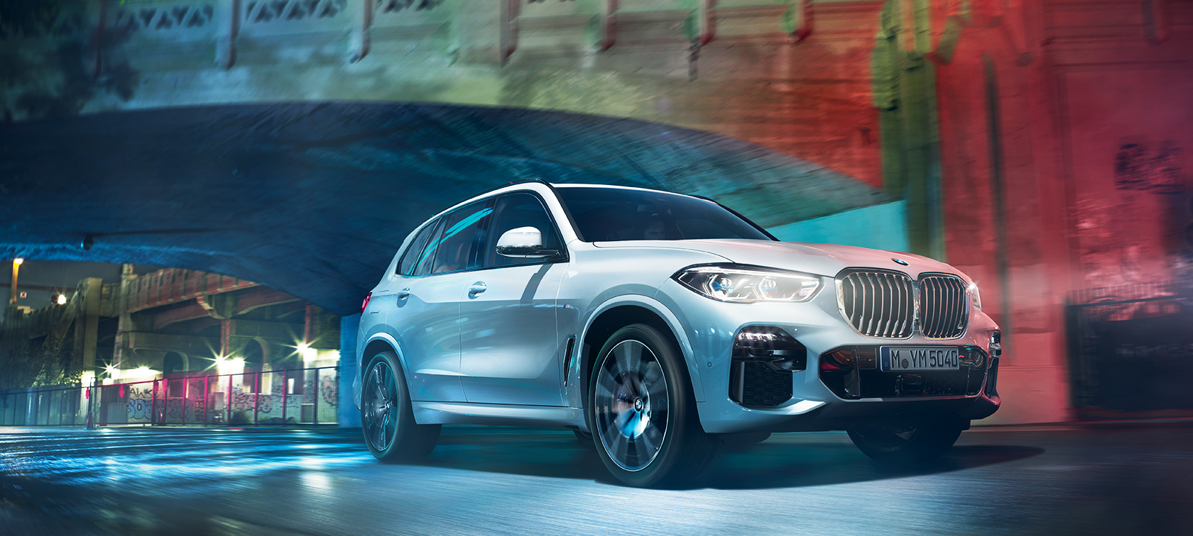The BMW X5 travelling through the city at night