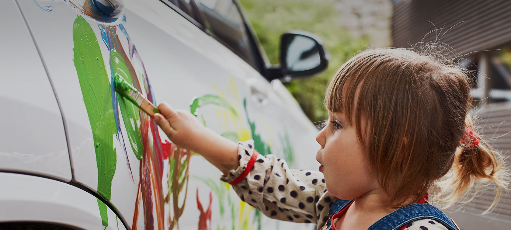 A little girl is painting a white BMW with colour.